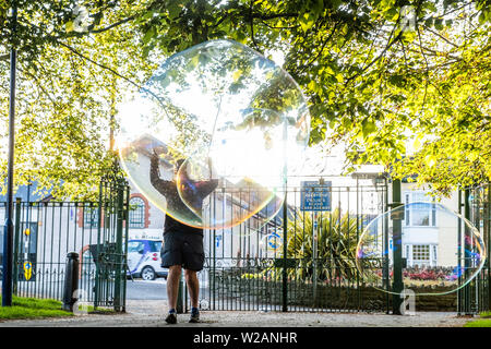 Aberystwyth Wales UK, Sunday 07 July 2019  UK Weather: A family in the park in Aberystwyth have fun making and playing  with giant soap bubble in the evening sunshine at the end of a warm summers day  in west Wales.   photo credit: Keith Morris/Alamy Live News - Stock Image