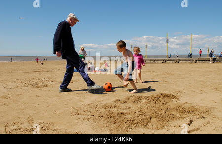Young Boy and Elderly Man Playing Football on Beach - Stock Image