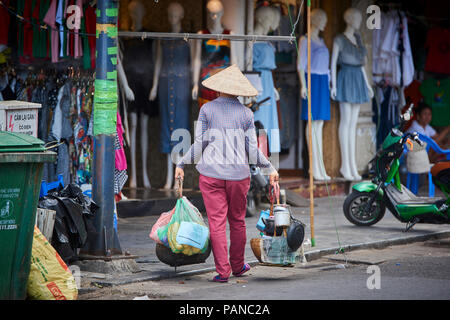 A woman carrying her merchandise in Hanoi, Vietnam, wearing a traditional conical hat. Women selling products on their bicycles are a common site in H - Stock Image