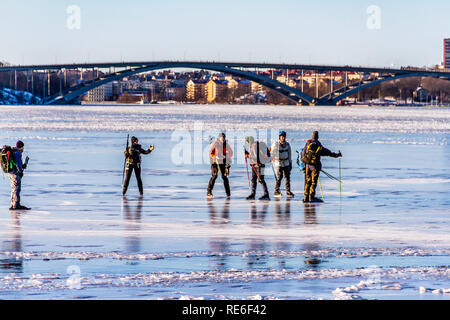 Ice skaters enjoying a sunny winter Sunday on Lake Malaren, in front of Vasterbron, the Western Bridge, Stockholm, Sweden. 20th January, 2019. - Stock Image