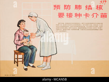 young mother in a pink stripe shirt holds a baby boy who is receiving a vaccine shot from a nurse dressed in white. - Stock Image