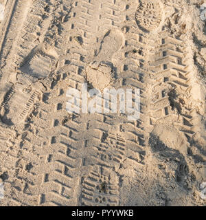 Mixture of footprints and tyre tracks on sandy beach. - Stock Image