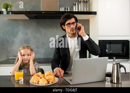 Unhappy daughter annoyed due to father work - Stock Image