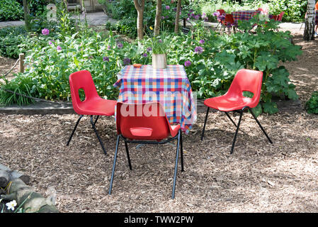 Empty table and red chairs, Dalston Eastern curve Garden, London Borough of Hackney. England, UK - Stock Image