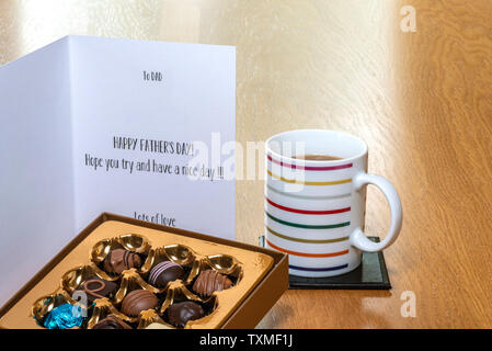 Fathers day card on wooden table with a box of chocolates, and a mug of coffee or tea. - Stock Image