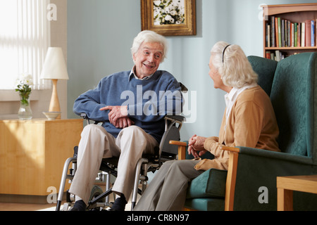 Senior couple in care home, man in wheelchair - Stock Image
