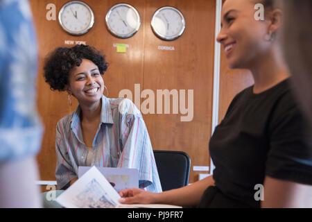 Creative businesswomen laughing in meeting - Stock Image
