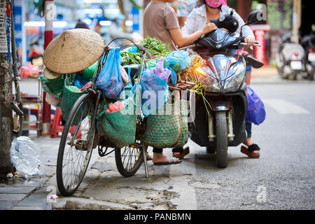 A parked bicycle in the Old Quarter district in Hanoi, Vietnam, with bags full of merchandise and conical straw hat hanging from it. - Stock Image