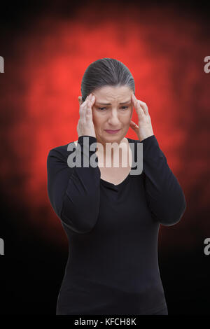 Middle aged woman with chronic pain syndrome fibromyalgia suffering from acute pain in the head, on red and black - Stock Image
