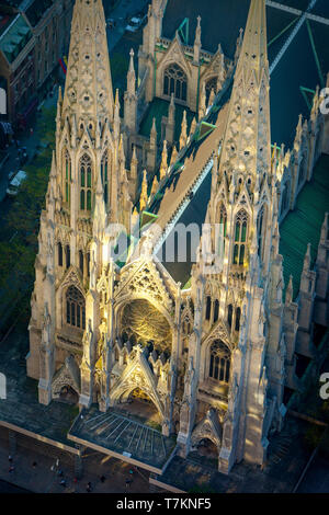 Overhead view of St. Patrick's Cathedral lit by early morning reflections from Rockefeller Center, Manhattan, New York City, USA - Stock Image