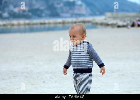 Beautiful Blond Baby Boy Wearing A Blue And White Sweater, Walking On The Sandy Beach, Close Up Portrait - Stock Image