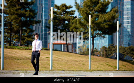 Businessman taking a walk at park - Stock Image