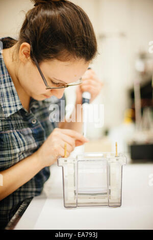 Close-up shot of female science student technician using burette - Stock Image