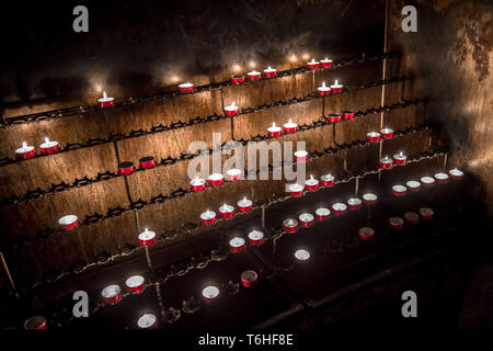 Red Memory Candles Burning In Chapel - Stock Image
