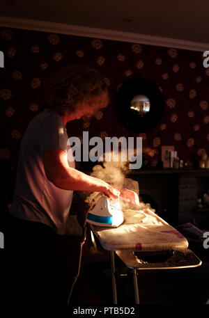 Woman using a Russell Hobbs steam iron - Stock Image