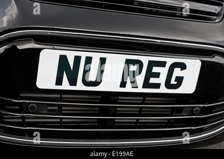 Registration plate on the front of a generic motorcar with 'Nu Reg' in black letters on white background for New car sales - Stock Image