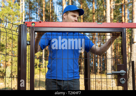 man check the level of new fence gates - Stock Image