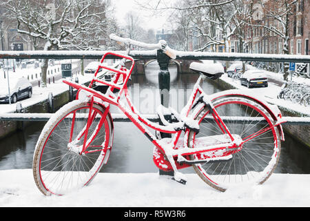 Red bike on a bridge in Amsterdam with snow. - Stock Image