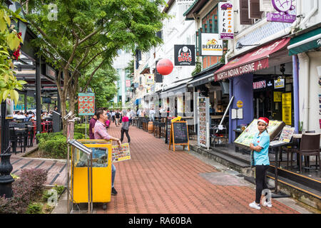 Singapore - 14th December 2018: Restaurant staff touting for business on Boat Quay. The street is popular with both tourists and expats. - Stock Image