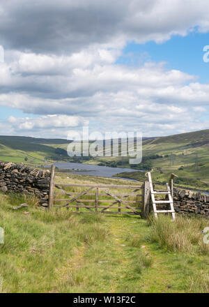 View over a five bar gate and stile towards Woodhead Reservoir from Crowden, Derbyshire, England, UK - Stock Image