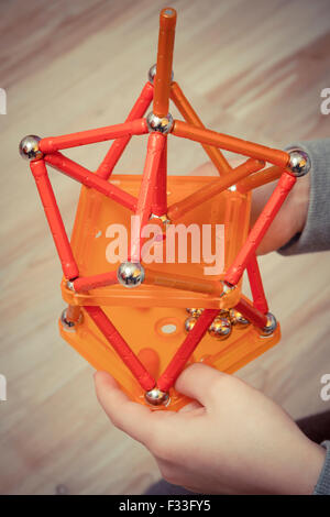 A young child holding a geometric toy. - Stock Image