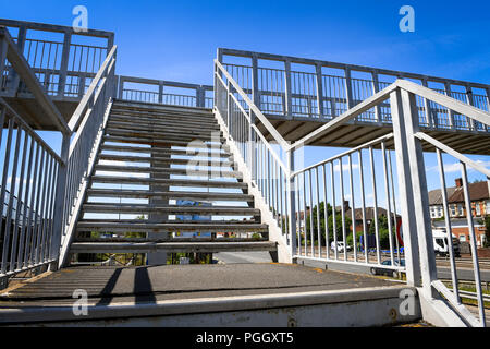 A metal stairway heading up to a footbridge crossing a busy road. - Stock Image