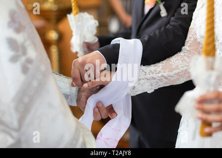 Hands of bride and groom tied together during wedding ceremony - Stock Image