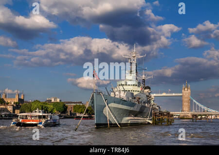 HMS Belfast museum ship moored on River Thames with The Tower of London, passing RB1 River Boat and Tower Bridge behind London SE1 - Stock Image