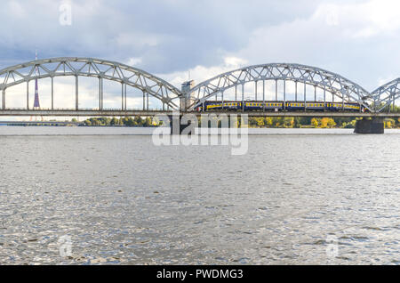 Latvian Railway train passing over the Railway bridge, Riga, Latvia, over the Daugava river - Stock Image