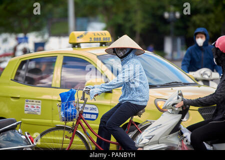 A cyclist in Hanoi, Vietnam, wearing traditional conical straw hat amongst heavy traffic. The iconic hat is worn mostly by women in the Northern part  - Stock Image
