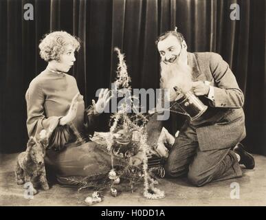 Woman watching man in fake beard watering Christmas tree - Stock Image