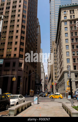 A view up Wall Street in New York City, NY, USA, United States of America. - Stock Image