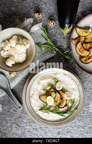Delicious cauliflower puree with baked eggplant and quail eggs - Stock Image