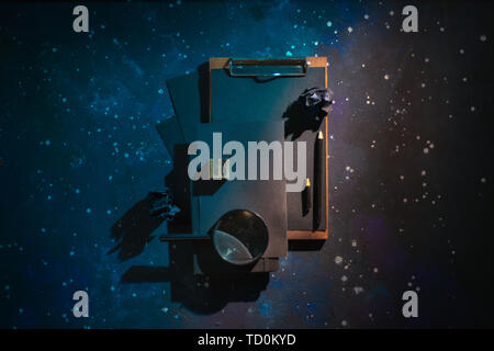 Black on black flat lay with a clipboard, notes and a magnifying glass. Starry sky background. Writing a science paper concept - Stock Image