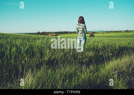 Young woman alone in a green field - Stock Image