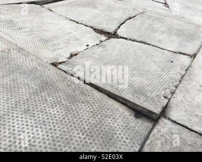 Broken slabs are a trip hazard often caused when goods vehicles mount the pavement. - Stock Image