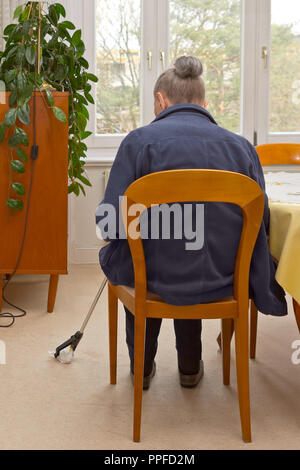 Rear view of an old woman sitting at a table picking something up from the floor, with a long-reach grabber device for elderly or disabled people. - Stock Image