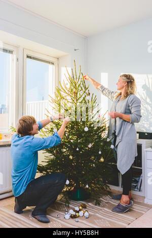 Finland, Helsinki, Couple decorating christmas tree together - Stock Image