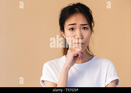 Photo of young japanese woman wearing basic t-shirt touching chin and looking at camera isolated over beige background in studio - Stock Image