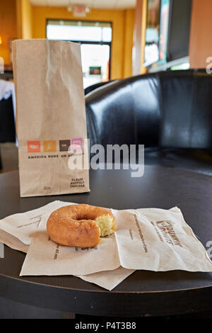 Bag of doughnuts or donuts with one plain partly or partially eaten donut on a napkin at Dunkin Donuts shop or store in Montgomery Alabama, USA. - Stock Image