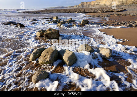 Sea foam on the shoreline at Monknash on the Glamorgan Heritage Coast, South Wales - Stock Image