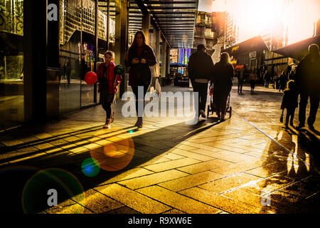 A low winter sun casts heavy shadows in a city street. - Stock Image