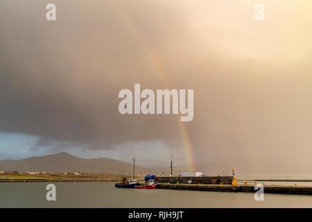 Dark clouds and rainbow over Valentia Island County Kerry, Ireland - Stock Image