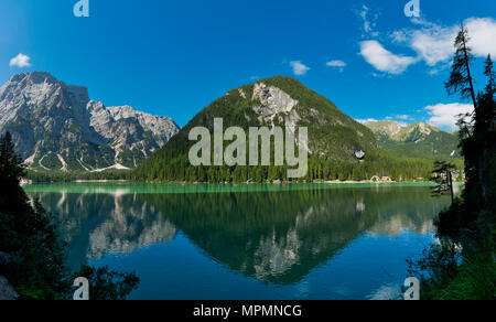 Braies lake in a clear day of summer season with mountains and blue sky in background, Dolomites - Italy - Stock Image