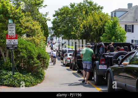 A long line of cars waits on local streets to take the Chappy Ferry to Chappaquiddick Island in Edgartown, Massachusetts on Martha's Vineyard. - Stock Image
