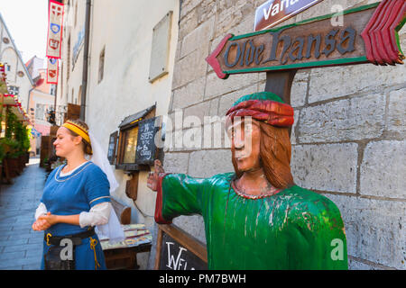 Tallinn restaurant, view of a colorful sign and a waitress in medieval dress outside the famous Olde Hansa restaurant in Tallinn Old Town, Estonia. - Stock Image