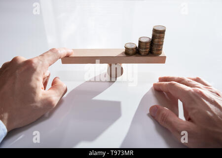 Close-up Of A Businessperson's Hand Balancing Stacked Coins On Wooden Seesaw With Finger Over Desk - Stock Image