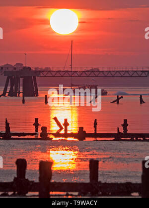 Sheerness, Kent, UK. 20th May, 2019. UK Weather: this evening's sunset in Sheerness in Kent. A man can be seen standing on the bow of a yacht returning at sunset, just as the pilot boat also happens to return at the same time. Credit: James Bell/Alamy Live News - Stock Image