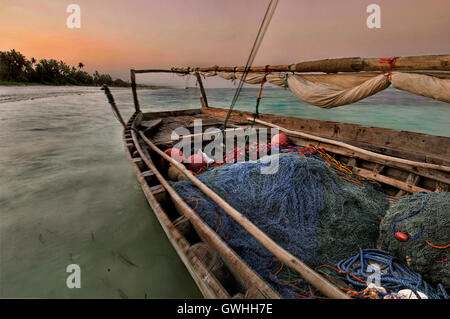 An old wooden fishing boat with nets floats on the ocean with sunset in background. Zanzibar, Tanzania. Africa. - Stock Image
