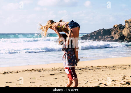Active happy couple carry and jump together in balance playful positions at the ebach enjoying the summer dy with sun and good weather - outdoor leisu - Stock Image